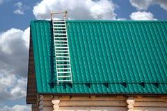 Een deel van nieuw buitenhuis van logboeken en het groene dak van de metaaltegel Stock Foto