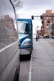 Een deel van nieuwe blauwe semi vrachtwagen met doosaanhangwagen op bezige stadsstraat Royalty-vrije Stock Afbeelding