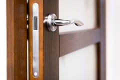 Een deel van open deur met zilveren deurkruk Stock Foto