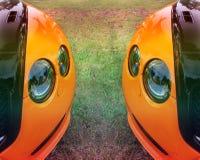 Een deel van een oranje auto op een achtergrond van gras Oranje luxeauto royalty-vrije stock fotografie