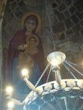 Een deel van een oude kroonluchter van ijzer met op het plafond de maagdelijke schets van ` s met het kind van Christus in een kl Stock Foto's