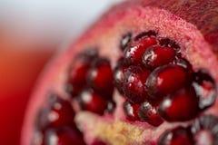 Een deel van een sappige granaatappel met zadenclose-up royalty-vrije stock afbeelding