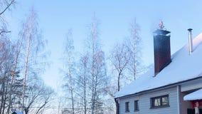 Een deel van snow-covered dak van huis met schoorsteen waarvan er rook is stock videobeelden