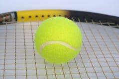 Een deel van tennisracket met gele bal CLO Stock Afbeeldingen