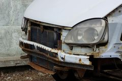 Een deel van een verpletterde auto met een radiator en koplamp op de straat royalty-vrije stock afbeeldingen