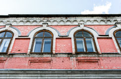 Een deel van voorgevel van de oude bouw met roze gebarsten bakstenen muren en Royalty-vrije Stock Foto's