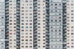 Een deel van een witte en grijze bakstenen muur met een groep gekleurde vensters en grijze balcones Horizontale textuur van gekle royalty-vrije stock fotografie