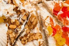 Een deel van zoete cake met een okkernoot, een room en een fruit Stock Fotografie
