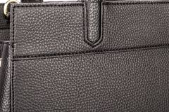 Een deel van een zwarte leerhandtas met handvatten en textuur royalty-vrije stock fotografie