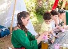 Een deelnemer in het ridderfestival toont bezoekers hoe te om aromatische drugs in Goren-park in Israël voor te bereiden Royalty-vrije Stock Afbeeldingen