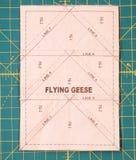 Een dekbedpatroon riep vliegende die ganzen aan de achterkant van de stof in een geroepen proces worden genaaid document het same stock foto's