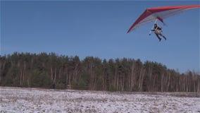 Een deltavlieger landt op een snow-covered weide stock videobeelden