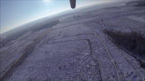 Een deltavlieger stijgt over een sneeuw de winterweide en een bos op stock videobeelden