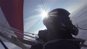 Een deltavlieger vliegt in de zonnige hemel over een sneeuw de winterweide en een bos stock footage