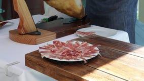 Een deskundige mens die Iberican-ham snijden stock footage