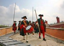 Een detachement van historische reenactors in groene en rode eenvormig van de 18de eeuw, markerwidth met wapens en slagwerker Stock Afbeeldingen