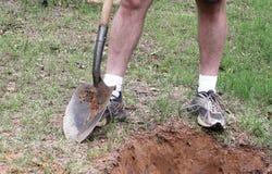 Een detail van man benen met een spade Stock Afbeeldingen