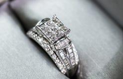 Een diamantverlovingsring in een doos met glint/bezinning Flikkerende prinses-besnoeiing diamanten stock afbeeldingen