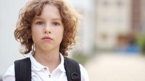 Een dicht portret van een ernstige blauw-eyed schooljongen met krullend haar De jongen is bezorgd en droevig Terug naar School stock footage