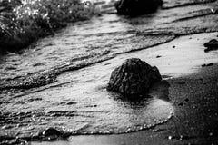 Een dichte mening van een meerkust, met details van water borrelt en stock fotografie
