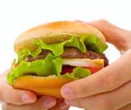 Een dichte omhooggaande cheeseburger die in handen wordt gehouden royalty-vrije stock foto