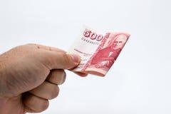 Een dichte omhooggaande foto van een Kaukasische mannelijke hand die een 500 Ijslandse kronennota houden Stock Foto