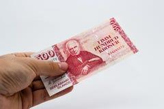 Een dichte omhooggaande foto van een Kaukasische mannelijke hand die een 500 Ijslandse kronennota houden Stock Foto's