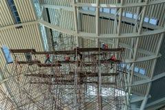 Een dichte omhooggaande mening van een bouwwerf waar een nieuw gebouw wordt geconstrueerd en zij hebben rijen en rijen van steige stock foto's