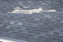 Een dichte omhooggaande mening van dakspanen een dakschade Dakdakspanen - Dakwerk Stock Foto's