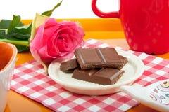 Een dienblad met chocolade en roze nam toe Stock Fotografie