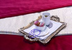 Een dienblad met een witte kop en een melkkruik op fluweel en brokaat stock afbeelding