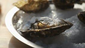 Een dienblad van ijs met oesters wordt gevuld die