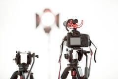 Een digitale videocamera met een microfoon op een driepoot op een witte achtergrond, een heldere schijnwerper in de achtergrond royalty-vrije stock afbeeldingen