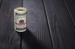 Een dik broodje van honderd dollarsbankbiljetten bond een rood elastiekje ligt op de zwarte houten lijst stock fotografie