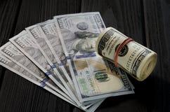 Een dik broodje van oude honderd dollarsbankbiljetten bond een rood elastiekje ligt op de bakkebaard van nieuwe honderd dollarsre stock fotografie