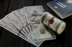 Een dik broodje van oude honderd dollarsbankbiljetten bond een rood elastiekje ligt op de bakkebaard van nieuwe honderd dollarsre royalty-vrije stock foto