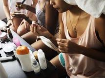 Een diverse groep vrouwen die en make-upn voorbereiden gebruiken stock afbeeldingen