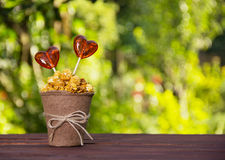Een document kop met karamelpopcorn en suikergoed Lollys in de vorm van hart Stock Foto's