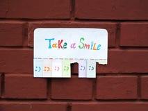 Een document met de uitdrukking: Neem een Glimlach en met een glimlach weg scheurde het teken klaar te zijn Royalty-vrije Stock Fotografie