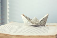 Een document schip wordt verzonden naar de weg van kennis en woorden op overzeese boekachtergrond royalty-vrije stock foto's