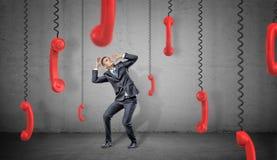 Een doen schrikken zakenman op concrete huiden als achtergrond van vele rode retro telefoonontvangers die neer op hun koorden han Stock Afbeeldingen