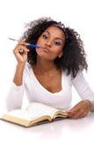 Een donker-gevilde vrouw met een notitieboekje Stock Foto's