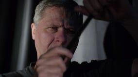 In een donker ruimteclose-up een mens die door een oude filmstrook kijken stock video