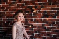Een donkerbruin meisje in het mooie kleding stellen tegen een achtergrond van een authentieke bakstenen muur stock foto