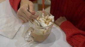Een donkerbruin meisje met lange haardranken met genoegen hete chocolade met heemst en slagroom in een koffie stock footage