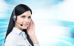 Een donkerbruine exploitant van de steuntelefoon in hoofdtelefoon Stock Foto's