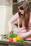 Een donkerbruine vrouw bevindt zich in de keuken dichtbij een lijst met verse groenten en de groenten van een messenwijze Royalty-vrije Stock Afbeeldingen