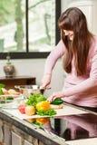 Een donkerbruine vrouw bevindt zich in de keuken dichtbij een lijst met verse groenten en de groenten van een messenwijze Royalty-vrije Stock Afbeelding