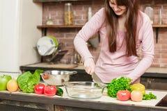 Een donkerbruine vrouw bevindt zich in de keuken dichtbij een lijst met verse groenten en de groenten van een messenwijze Stock Foto's