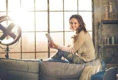 Een donkerbruine vrouw glimlacht in een zolderwoonkamer Stock Foto's